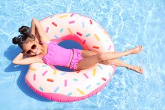 Little girl with inflatable ring in pool stock photography