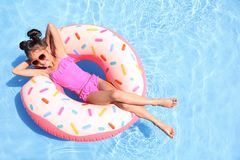 Little girl with inflatable ring in pool stock image