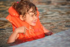 Little girl in inflatable waistcoat in pool. Smiling little girl in inflatable lifejacket in pool royalty free stock photography