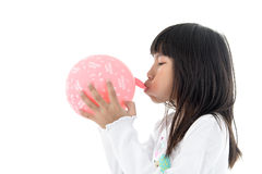 Little Girl inflate a Pink Balloon with Happy birthday message o Royalty Free Stock Images