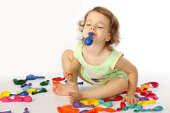 A little girl inflates balloons. Royalty Free Stock Photo