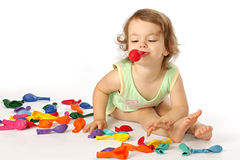 A little girl inflates balloons. A little girl inflates coloured balloons Stock Photo
