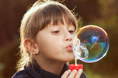 Little girl inflates a big bubble Stock Images