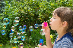 Little girl inflates soap bubbles Royalty Free Stock Photo