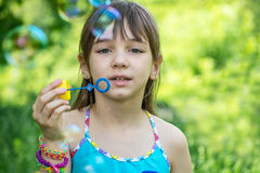 Little girl inflates soap bubbles Stock Photography