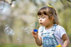 Little girl inflates soap bubbles. In spring in the garden Stock Photography