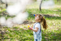 Little girl inflates soap bubbles. In spring in the garden Stock Photo