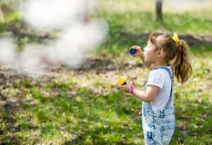 Little girl inflates soap bubbles. In spring in the garden Royalty Free Stock Photos