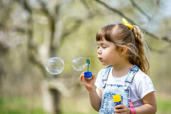 Little girl inflates soap bubbles. In spring in the garden Royalty Free Stock Photography