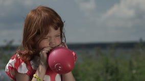Little girl inflating balloon stock video