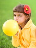 Little girl is inflating yellow balloon. Outdoors Royalty Free Stock Image