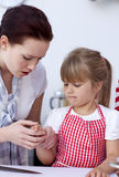 Little girl injured by a knife in kitchen Stock Photo