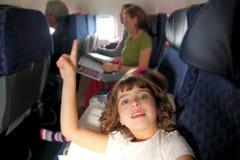 Little girl inside aircraft rising up finger. Smiling stock images