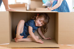Little girl inside box in new flat after moving. Child little girl inside box in new flat after moving Stock Photos