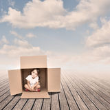 Little girl inside a Box. On a pier stock images