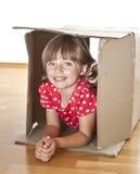Little girl inside a cardboard box. Little girl playing inside a cardboard box Royalty Free Stock Images