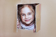 Little girl inside cardboard playhouse Royalty Free Stock Image