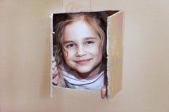 Little girl inside cardboard playhouse. Smiling little girl inside cardboard playhouse Royalty Free Stock Image