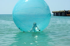Little girl inside a giant balloon on the sea surface Stock Photo