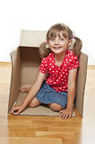 Little girl inside a paper box Stock Images