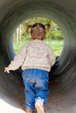 Little Girl Inside Tunnel. Little girl running away through the big tube on a playground royalty free stock photography