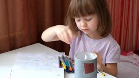 Little girl with an intelligent look draws scrawl stock video