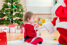 Little girl interacting with Santa Claus by the Christmas tree Royalty Free Stock Photo