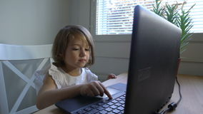 Little girl with interest uses the laptop sitting at the table. Dolly shot. Slow motion stock footage