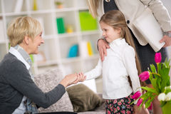 Little girl introduction her new babysitter. Girl timidly shake hands with mature woman royalty free stock photos