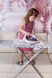 Little girl irons clothes Stock Images