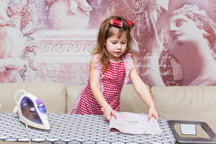 Little girl irons clothes Royalty Free Stock Images