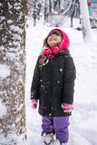 Little girl in jacket and knitted hat catching snowflakes in winter park on Christmas. stock photo