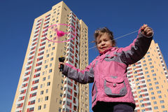 Little girl in jacket, plays with propeller Royalty Free Stock Photo