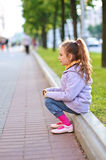 Little girl in jacket sitting on Stock Photography