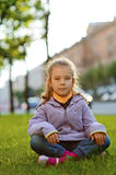 Little girl in jacket sitting on Stock Photo
