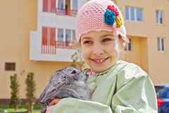 Little girl in  jacket stands holding rabbit Stock Photos