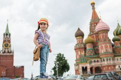 The little girl in jeans and cap with straw bag. Stands near the Kremlin royalty free stock images