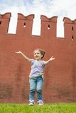 Little girl in jeans have fun on the grass. Near old brick wall royalty free stock image