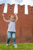 Little girl in jeans have fun and raised hands up. Near old brick wall stock image