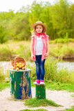 Little girl in jeans and a shirt near a river  with apples Stock Images