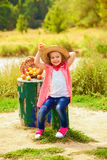 Little girl in jeans and a shirt near a river  with apples Royalty Free Stock Photography
