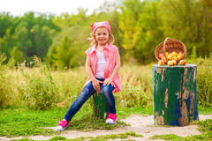 Little girl in jeans and a shirt near a river  with apples Stock Image