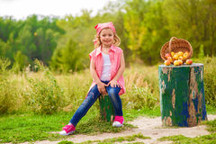 Little girl in jeans and a shirt near a river  with apples Royalty Free Stock Image