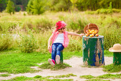 Little girl in jeans and a shirt near a river  with apples Stock Photography
