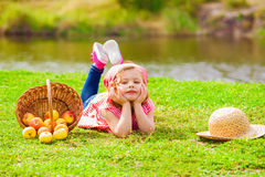 Little girl in jeans and a shirt near a river  with apples Stock Photo