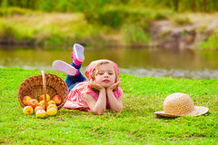 Little girl in jeans and a shirt near a river  with apples Royalty Free Stock Photo