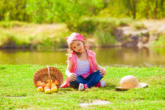Little girl in jeans and a shirt near a river  with apples Royalty Free Stock Photos
