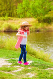 Little girl in jeans and a shirt near a river Stock Image