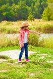 Little girl in jeans and a shirt near a river Royalty Free Stock Image