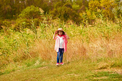 Little girl in jeans and a shirt near a river Stock Images